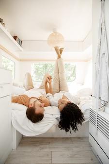 Amore coppia scherzare nel letto del camper, in campeggio in una roulotte. uomo e donna viaggiano in furgone, vacanze in camper, svaghi campeggiatori in camper