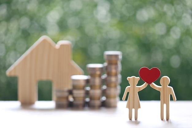 Amore coppia che tiene la forma del cuore e la pila di monete soldi con il modello di casa su sfondo verde naturale
