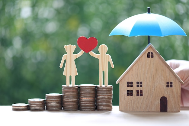 Amore coppia tenendo la forma del cuore in piedi su una pila di monete soldi con casa modello sotto l'ombrellone su sfondo verde naturale