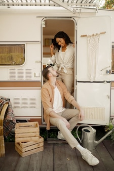 Amore coppia abbracci in camper, campeggio in una roulotte. l'uomo e la donna viaggiano in furgone, vacanze in camper, svaghi in camper