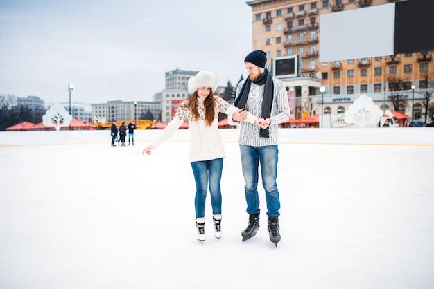 La coppia di innamorati impara a pattinare sulla pista. pattinaggio invernale all'aria aperta, tempo libero attivo, pattinaggio sul ghiaccio