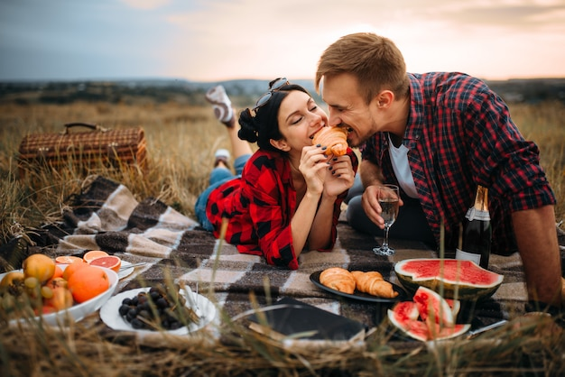 Amore coppia per il tempo libero insieme, picnic sul prato. giuncata romantica, uomo e donna sulla cena all'aperto, felice fine settimana in famiglia
