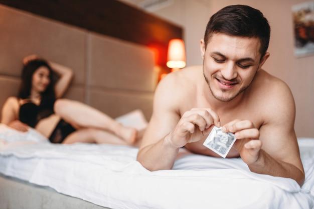 Amore coppia sdraiata a letto, uomo sorridente tiene un preservativo in mano.