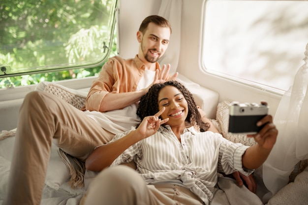 La coppia di innamorati fa selfie nel letto del camper, in campeggio in una roulotte. uomo e donna viaggiano in furgone, vacanze in camper, svaghi campeggiatori in camper