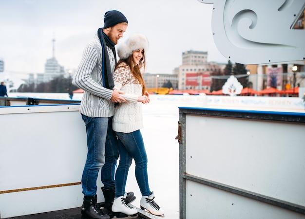 La coppia di innamorati si prepara a pattinare sulla pista. pattinaggio invernale all'aria aperta, tempo libero attivo, pattinaggio sul ghiaccio