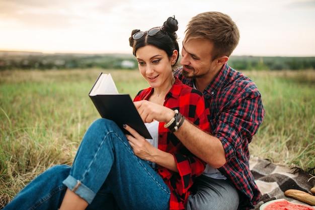 La coppia di amore legge il libro insieme, picnic nel campo. giuncata romantica, uomo e donna sulla cena all'aperto, felice fine settimana in famiglia