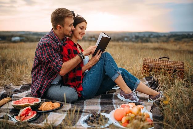 La coppia di amore legge il libro insieme, picnic sull'erba. giuncata romantica, uomo e donna sulla cena all'aperto, felice fine settimana in famiglia