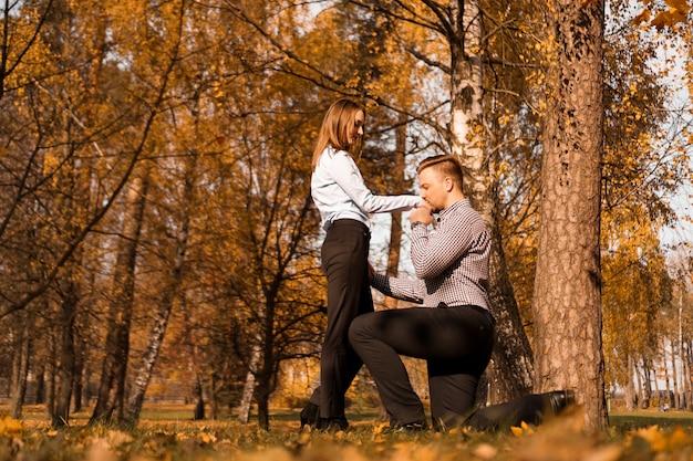 Amore, coppia, relazione e concetto di fidanzamento - l'uomo in ginocchio bacia una mano una donna nel parco d'autunno