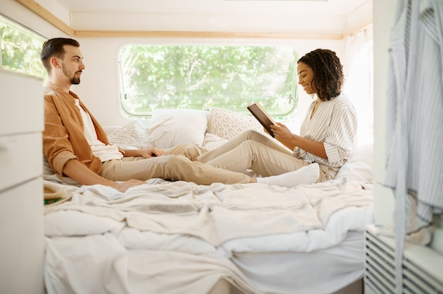 Amore coppia rilassarsi in camera da letto, campeggio in una roulotte. uomo e donna viaggiano in furgone, vacanze in camper, svaghi campeggiatori in camper
