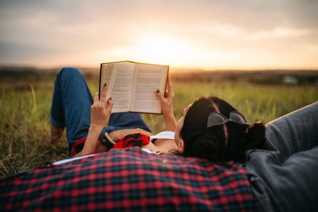 Coppie di amore che riposano insieme, picnic nel campo. giuncata romantica sul tramonto, uomo e donna sulla cena all'aperto, felice fine settimana in famiglia