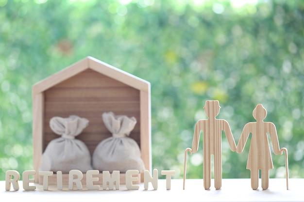 Amore coppia senior e casa modello con monete soldi nella borsa su naturale su sfondo verde
