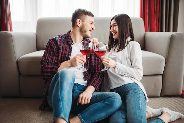 Amore coppia seduta sul pavimento contro il divano, guarda film e beve vino rosso da grandi bicchieri, finestre e interni del soggiorno