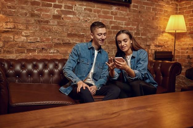 Amore coppia seduta sul divano nella barra del narghilè