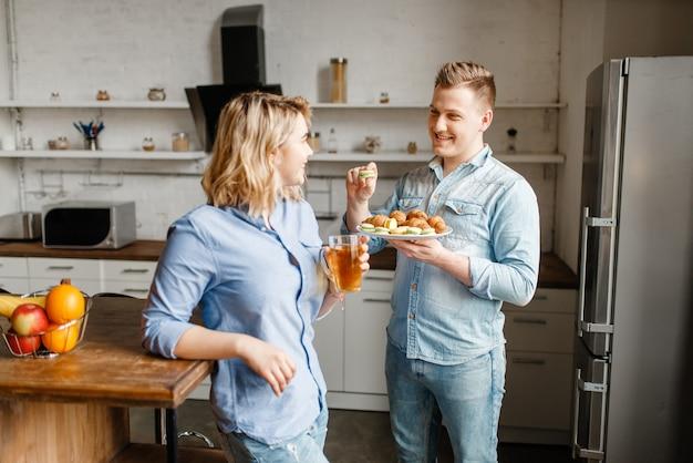 Amore coppia con croissant e biscotti, colazione romantica.