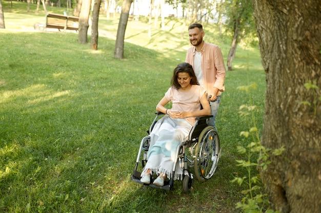 Amore coppia con sedia a rotelle che cammina nel parco autunnale