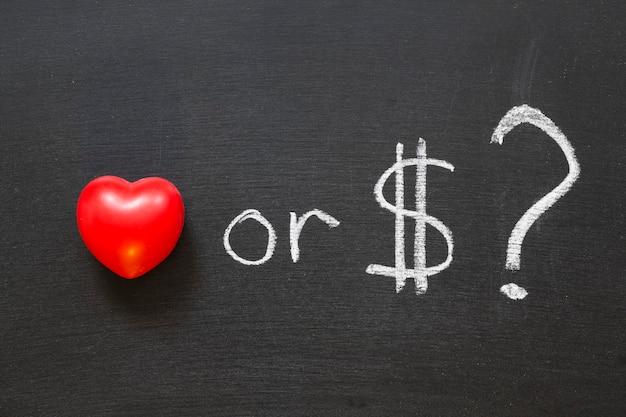 Amore o dollari? frase scritta a mano sulla lavagna della scuola