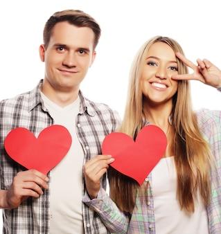 Concetto di amore, famiglia e persone: coppia felice innamorata che tiene il cuore rosso