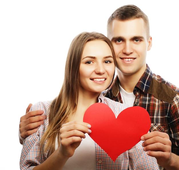 Concetto di amore, famiglia e persone: coppia felice innamorata che tiene cuore rosso.