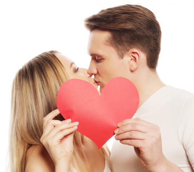 Concetto di amore, famiglia e persone: coppia felice innamorato che tiene cuore rosso