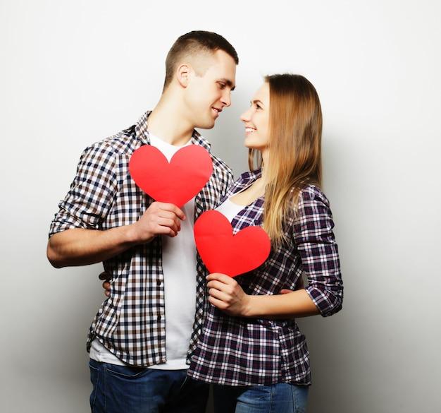 Concetto di amore, famiglia e persone: coppia felice innamorato che tiene cuore rosso.