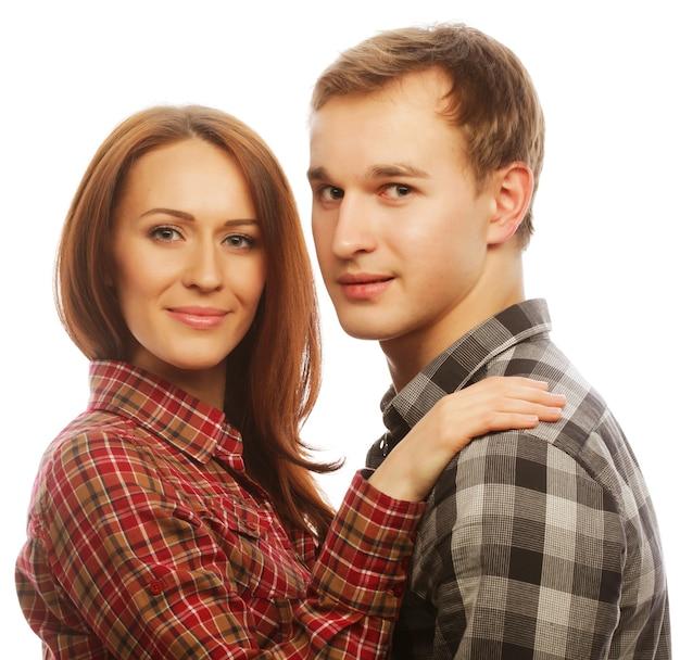Concetto di amore, famiglia e persone: bella coppia felice che abbraccia su sfondo grigio.