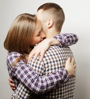 Concetto di amore, famiglia e persone: adorabili coppie felici che abbracciano sul grigio.