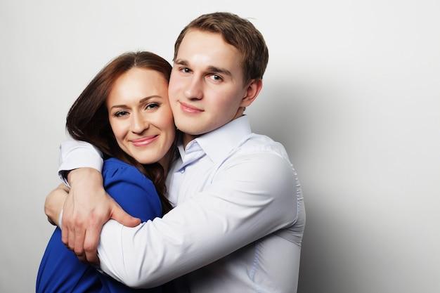 Concetto di amore, famiglia e persone. bella coppia felice abbracciando su grigio