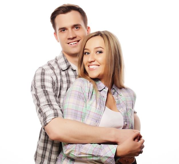Concetto di amore, famiglia e persone: coppia felice adorabile che abbraccia sopra priorità bassa bianca.