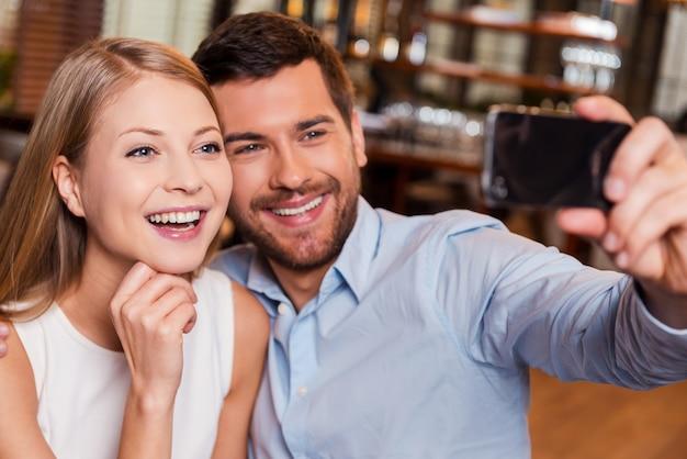 Amore a fuoco. bella giovane coppia di innamorati che fa selfie e sorride mentre si siede al ristorante insieme