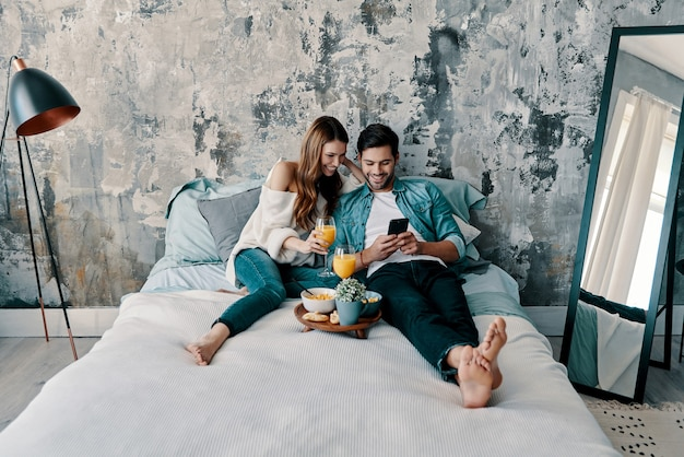 Amore per sempre. bella giovane coppia che fa colazione mentre trascorre il tempo a letto a casa