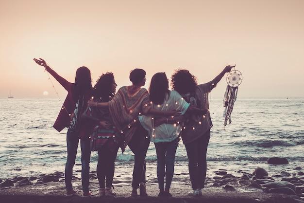 Amo l'amicizia e l'immagine del concetto di tempo di celebrazione con un gruppo di amiche viste da dietro godendosi il bellissimo tramonto colorato di fronte all'oceano - sentirsi con la natura e gioiosi per il mondo