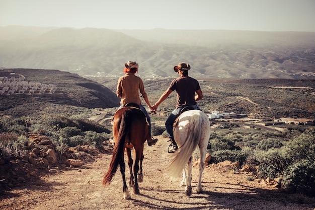 Concetto di amore e amicizia all'aperto per le persone che vanno a cavallo in campagna. paesaggi meravigliosi e un mondo da scoprire viaggiando insieme. uomo e donna caucasici