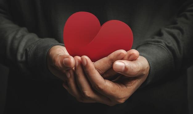 Amore, assistenza sanitaria, donazione e concetto di beneficenza. primo piano del volontario che tiene una carta a forma di cuore