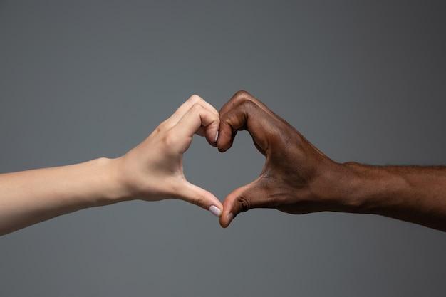 Gesto del cuore di amore. tolleranza razziale. rispetta l'unità sociale. mani africane e caucasiche che gesturing su sfondo grigio studio. diritti umani, amicizia, concetto di unità internazionale. unità interrazziale.