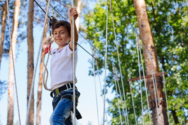 Altezza dell'amore. allegro ragazzo preadolescenziale che sorride alla telecamera mentre si muove con sicurezza nel parco avventura