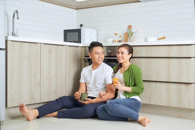 L'amore è nell'aria. belle giovani coppie che bevono caffè e succo d'arancia mentre erano seduti sul pavimento della cucina a casa