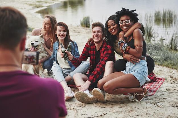 L'amore è nell'aria. un gruppo di persone fa un picnic sulla spiaggia. gli amici si divertono durante il fine settimana.
