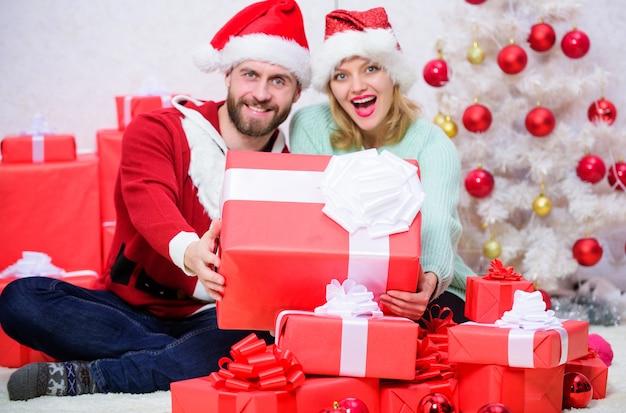 L'amore è il miglior regalo. coppia sposata di famiglia a casa. le coppie innamorate si godono la celebrazione delle vacanze invernali. vigilia di natale con tesoro. la donna e l'uomo barbuto innamorati si siedono vicino allo sfondo dell'albero di natale.
