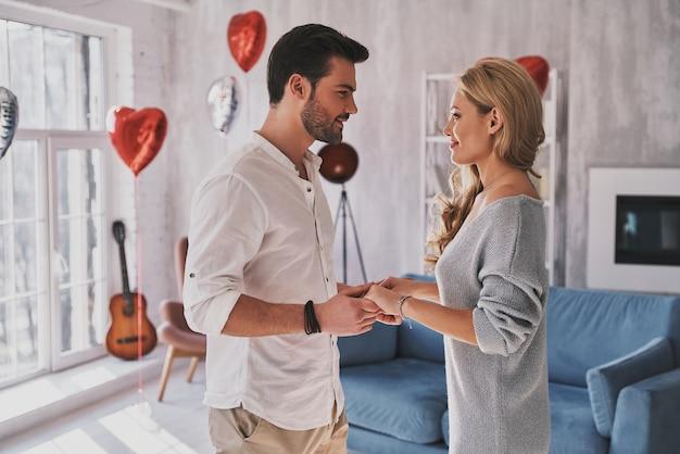 L'amore è il tesoro più grande. bella giovane coppia che si tiene per mano e si guarda con un sorriso mentre sta in piedi nella camera da letto piena di palloncini
