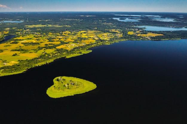 Isola dell'amore su un lago in europa, un'isola verde a forma di cuore su un lago scuro con un luccichio del sole.