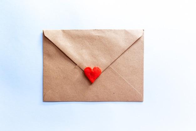 Lettera d'amore in una busta artigianale con cuore rosso argilla su sfondo azzurro.