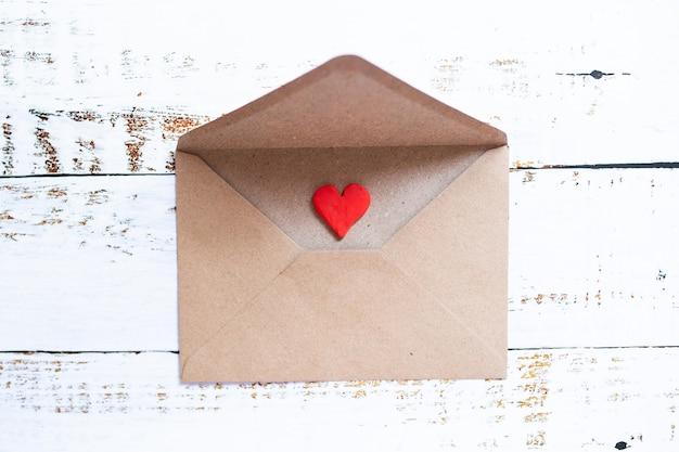 Lettera d'amore in una busta artigianale con cuore rosso argilla su fondo di legno bianco.