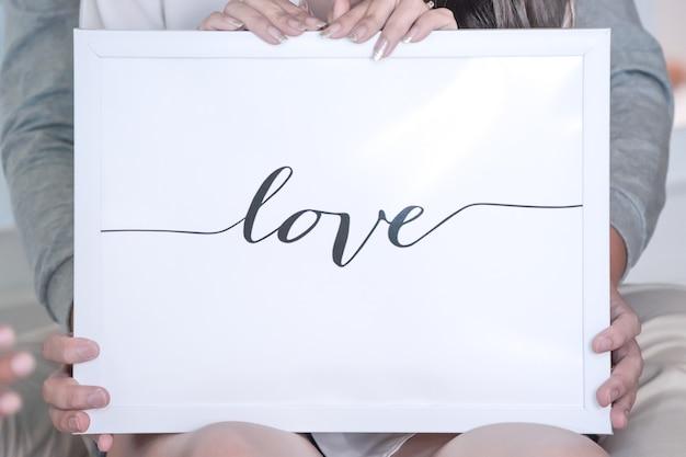 Lettera d'amore nella cornice bianca e sullo sfondo, trattenuta dalla sposa e dallo sposo dietro.