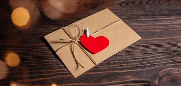 Lettera d'amore con un cuore su uno sfondo di luci, amore e concetto di san valentino su un tavolo di legno
