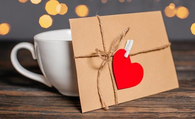 Lettera d'amore con un cuore accanto a una tazza su uno sfondo di luci, amore e concetto di san valentino su un tavolo di legno