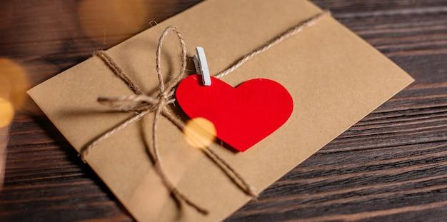 Lettera d'amore con un concetto di cuore, amore e san valentino su un tavolo di legno
