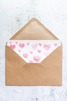 Lettera d'amore con cuori rosa color acqua in una busta artigianale su fondo di legno bianco.