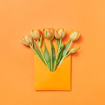Lettera d'amore giallo fiori appena colti in una busta fatta a mano su uno sfondo arancione con pizzo per il testo. lay piatto.