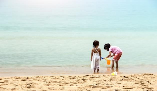 Momento d'amore della sorella che gioca insieme sulla spiaggia