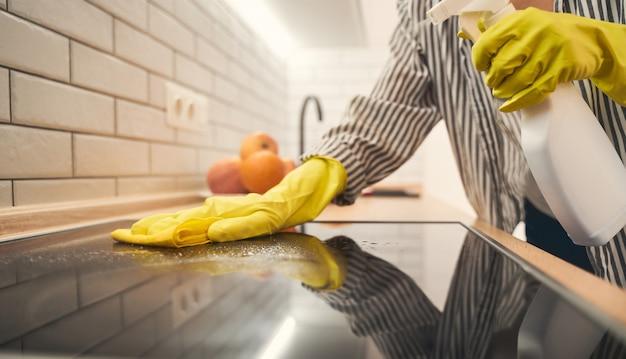 Amo la mia casa. giovane donna che è a casa e pulisce la superficie del vetro sul forno